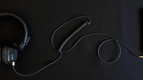 Black wired headphones with ear pads and a smartphone lie on a black background. Analog wire connection using mini-jack - 3.5 mm. Music and creativity