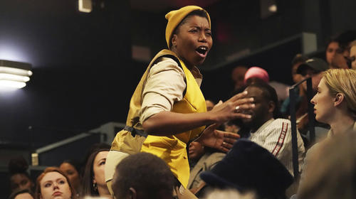A close-up shot of a black box theatre filled with audience members. In the center of the audience, a young, Black actor stands, mid-speech, They are wearing all yellow and gesturing with their open hands.